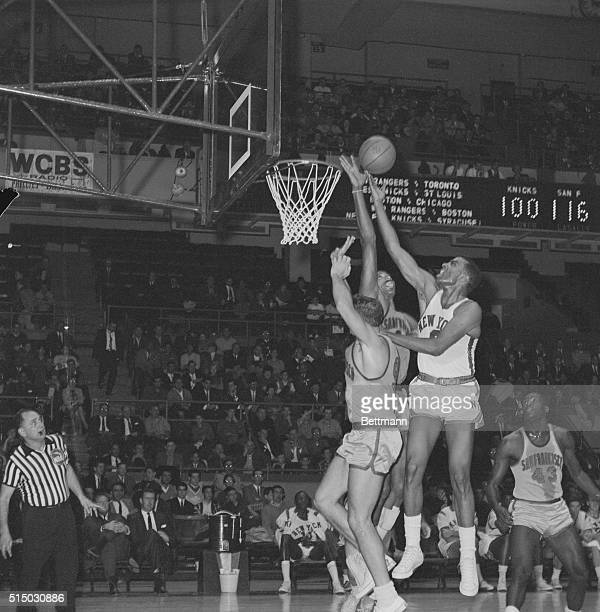 Stretching his arm high San Francisco Warriors' center Wilt Chamberlain prevents Willie Naulls of the New York Knickerbockers from scoring this...