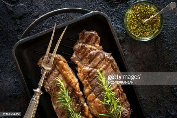 ニューヨークストリップステーキもグリルパンで焼いたボーンレストップロインステーキ - チミチュリ・ソース ストックフォトと画像