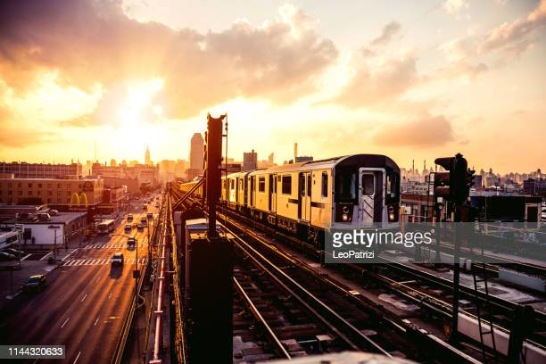 new york subway train approaching station platform in queens - railroad station stock pictures, royalty-free photos & images