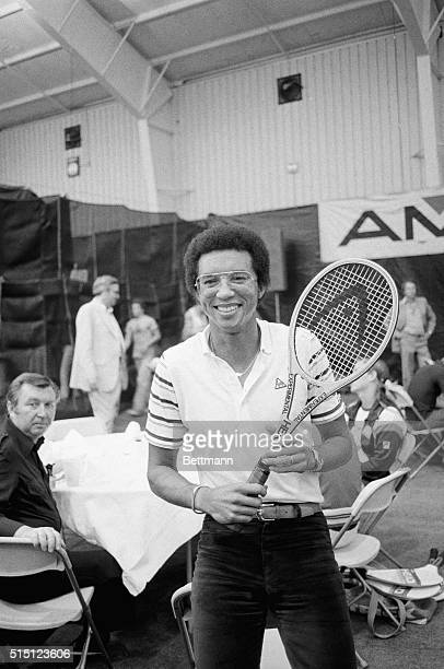 New York: Tennis great Arthur Ashe seems almost out of place with street clothes and a tennis racket, but he was on hand at the U. S. Open Tennis...