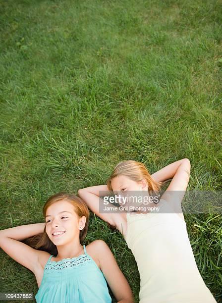 USA, New York, Two girls (10-11, 10-11) lying on grass backyard
