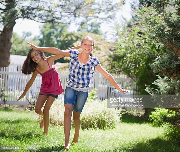 usa, new york, two girls (10-11, 10-11) playing in backyard - only girls stock pictures, royalty-free photos & images