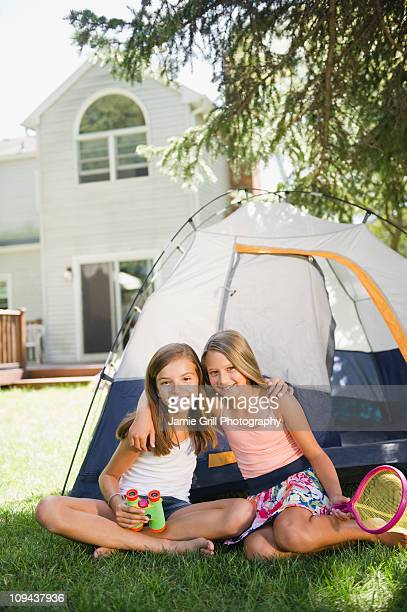 USA, New York, Two girls (10-11, 10-11) playing with tent in backyard