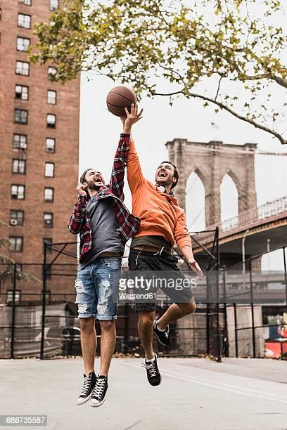 usa, new york, two young men playing basketball on an outdoor court - puente de brooklyn fotografías e imágenes de stock