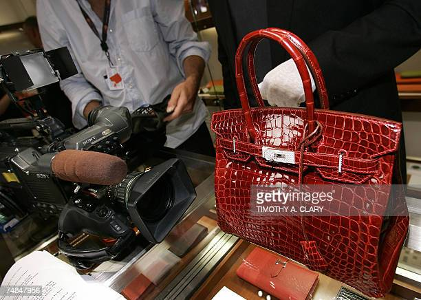 A employee holds displays a 129000 USD crocodile Hermes Birkin Bag for the press during a private opening for the new Hermes store on Wall Street in...