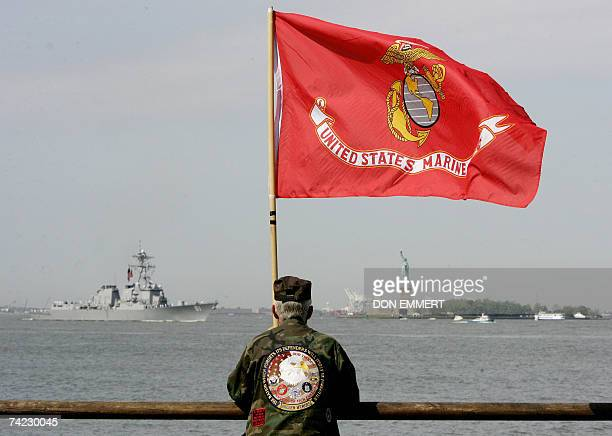 A man holding a US Marine Corp flag watches as ships sail past the Statue of Liberty in New York Harbor 23 May 2007 The Parade of Ships marks the...