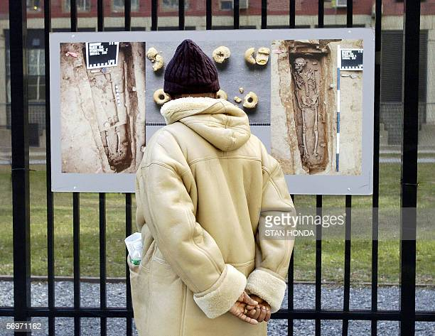 A man looks at a display of photographs showing graves at the African Burial Ground Memorial Site 01 March 2006 in the Lower Manhattan area of New...