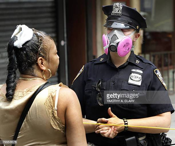 A New York City Police officer wears protective mask near the site of an underground steam pipe explosion 19 July 2007 in New York The 18 July...