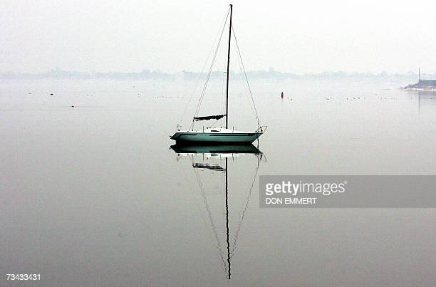 A sailboat is reflected in the calm waters off the shoreline of the Bronx 27 February 2007 in New York AFP PHOTO/DON EMMERT