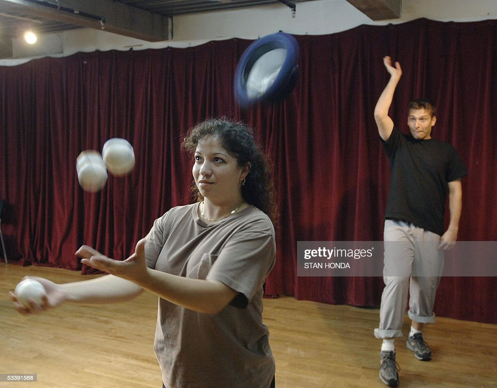 As Carmen Tellez (L) practices her juggling Christopher Lueck (R) tries to toss a hat onto her head at the New York Goofs Ultimate Clown School, 11 August 2005 in New York. The two-week session offers an intensive course of study in the art of clowning and is one of the few clown schools in the U.S. AFP PHOTO/Stan HONDA