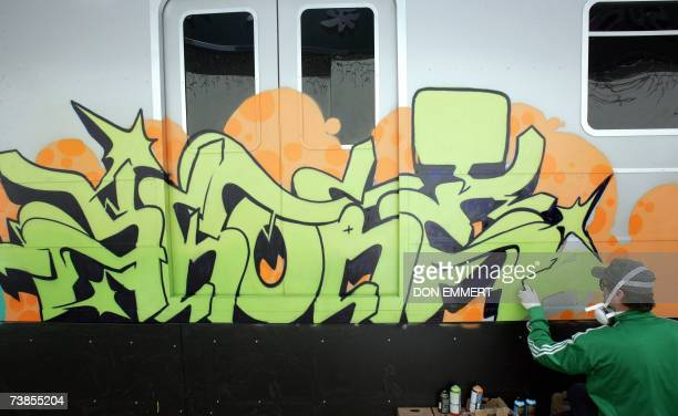 British graffiti artist Skore sprays paint on a replica of a subway car as part of an Adidas advertising campaign 10 April 2007 in New York Seven...