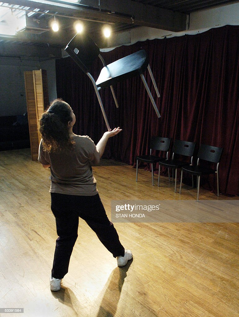 Carmen Tellez practices balancing a chair at the New York Goofs Ultimate Clown School, 11 August, 2005, in New York. The two week session offers an intensive course of study in the art of clowning and is one of the few clown schools in the U.S. AFP PHOTO/Stan HONDA
