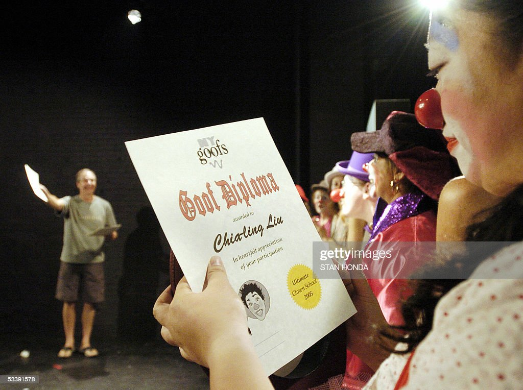 Chia-ling Liu of Taiwan (R) looks at her diploma given by Dick Monday (L) from the New York Goofs Ultimate Clown School after their performance before family and friends 14 August 2005 in New York. The two-week session offers an intensive course of study in the art of clowning and is one of the few clown schools in the U.S. AFP PHOTO/Stan HONDA