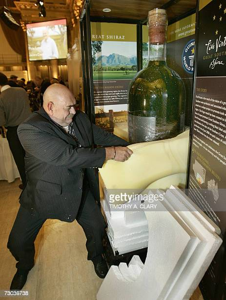 """New York, UNITED STATES: Concept founder Kim Bullock unpacks what is billed as """"the largest bottle of wine in the world"""", an almost 54-gallon bottle..."""