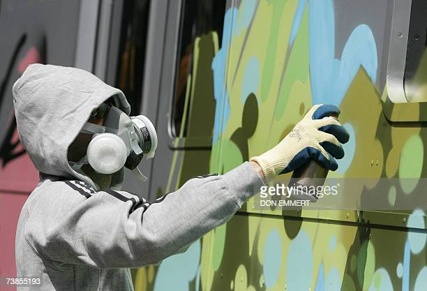 Italian graffiti artist Smart wears a mask as he sprays paint on a replica of a subway car as part of an Adidas advertising campaign 10 April 2007 in...