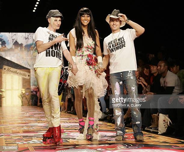 Kimora Lee Simmons displays an outfit from the Heatherette Fall 2007 collection beside designers Richie Rich and Traver Rains during Fashion Week at...