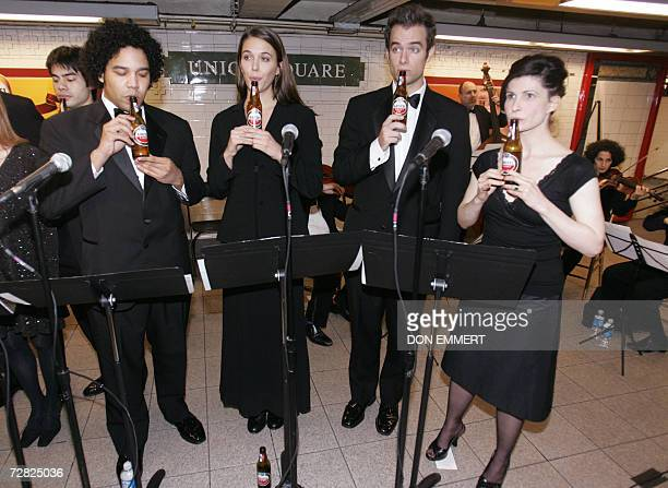 Members of The Live Tastefully Bottle Symphony perform holiday songs by blowing on Amstel Light bottles 14 December 2006 on a subway platform in New...