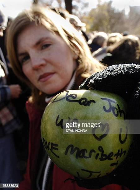 Michelle Vargas of New Jersey displays a green apple with a message to John Lennon from herself her sister Mary Beth and daughter Julia that she will...