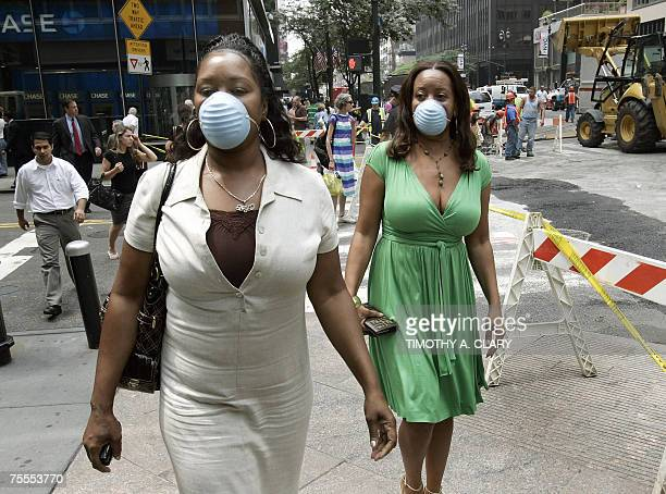 New York City business women wearing masks walk down the street 19 July 2007 one day after an underground steam pipe explosion tore through Lexington...