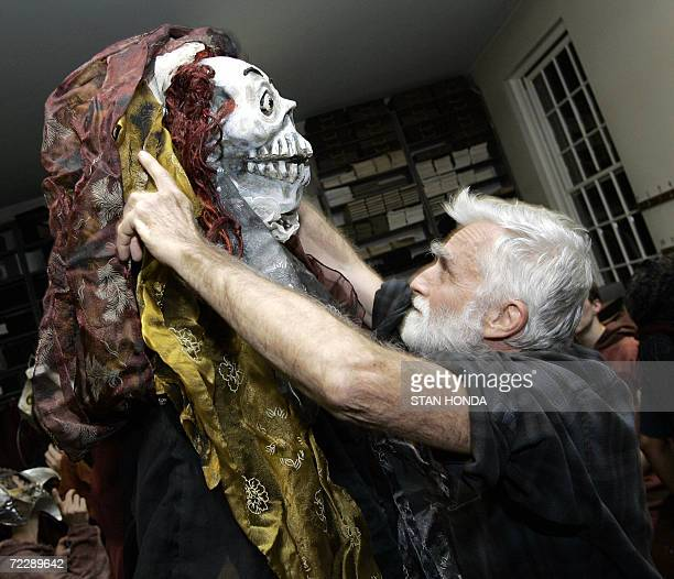 Puppet and mask maker and theater director Ralph Lee adjusts the mask on a creature backstage before The Grand Procession of the Ghouls at the...