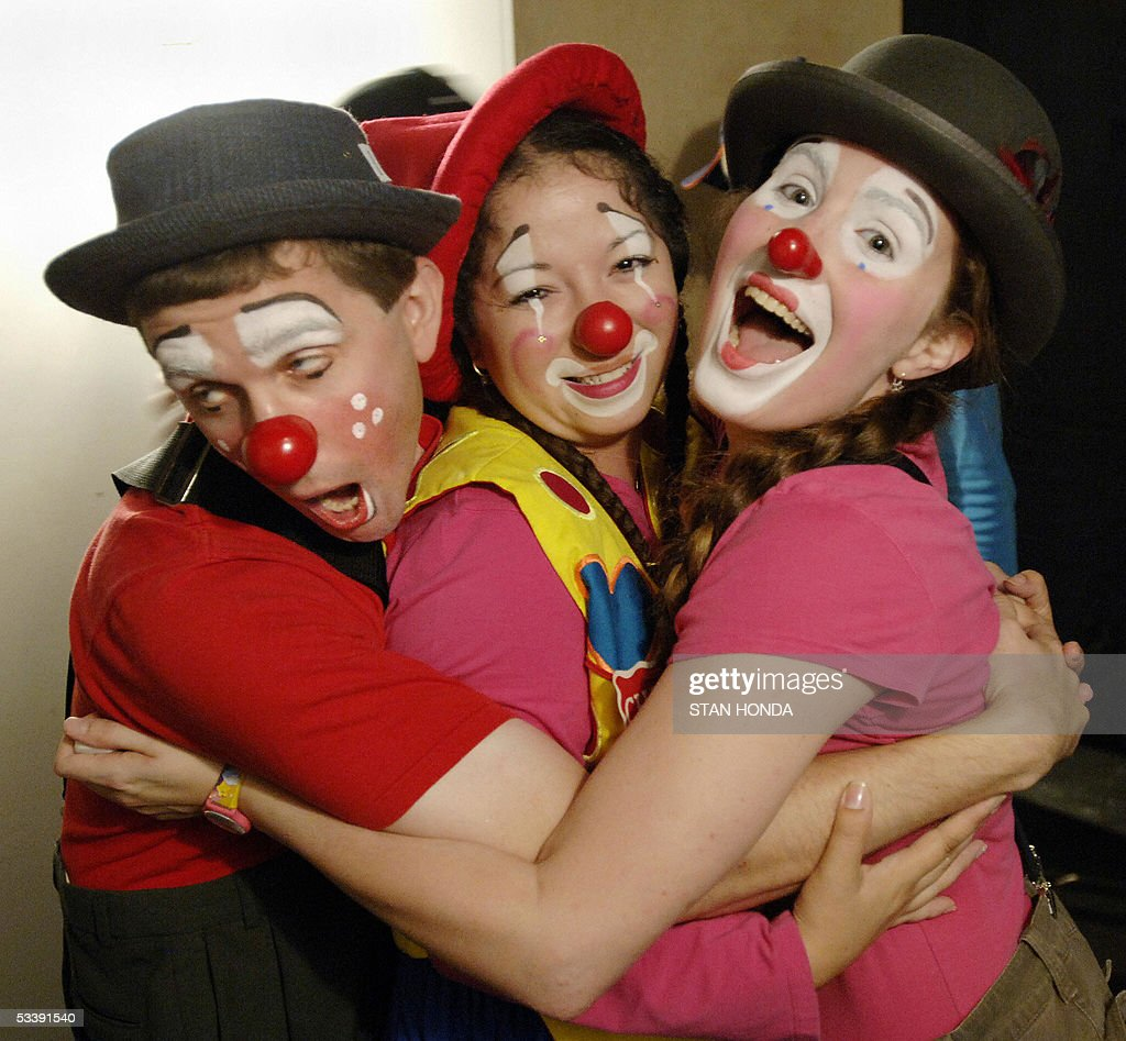Ryan O'Neil (L), Carmen Tellez (C) and Liz Dubuisson (R) hug each other just before a performance of the New York Goofs Ultimate Clown School 14 August 2005 in New York. The two-week session, which offers an intensive course of study in the art of clowning, is one of the few clown schools in the US. AFP PHOTO/Stan HONDA