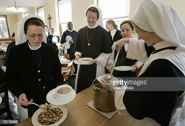 New York, UNITED STATES: Sister Giovanna Marie serves soup as Sister Mary Gabriel gets croutons during lunch at the Roman Catholic Sisters of Life...