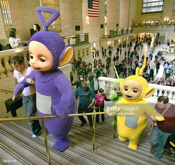 The world famous Teletubbies get helped back up the stairs after posing on the balcony at Grand Central Station in New York 26 March 2007 as they...