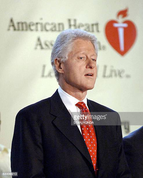 This 03 May 2005 photo shows former US President Bill Clinton stands in front of the logo of the American Heart Association during a visit to Public...