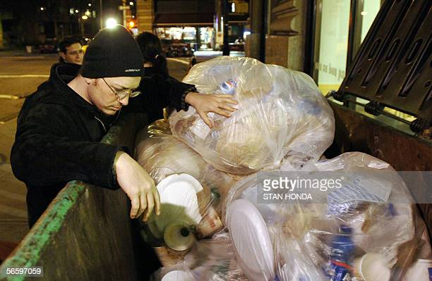 TO GO WITH AFP STORY BY CATHERINE HOURS Jason Samuels looks through a trash dumpster for edible food thrown out by an Au Bon Pain store 12 January in...