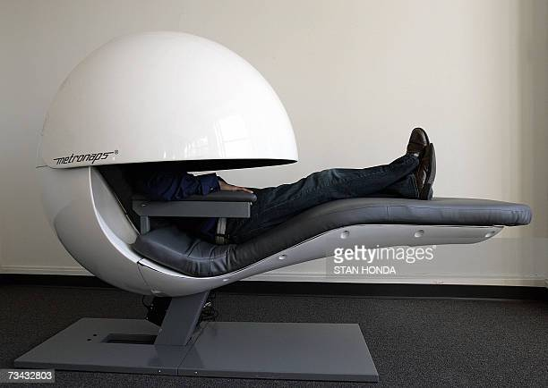 TO WITH AFP STORY BY VIGINIE MONTET Metronaps CEO Arshad Chowdhury demostrates a prototype sleeping pod with a retractable shield that covers the...