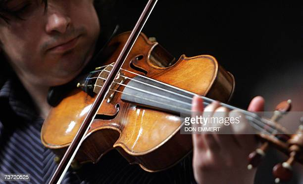 Violinist Adrian Pintea from The Julliard School plays a 1729 Stradivari known as the 'Solomon ExLambert' 27 March 2007 at Christie's in New York The...