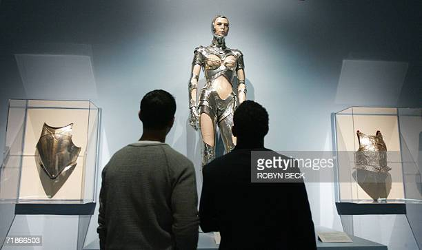 Visitors view a piece called Robot Couture a silver cyborg outfit by designer Thierry Mugler piece at the Love and War The Weaponized Woman...