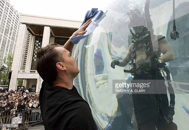 Workers clean the glass sphere of magician David Blaine encased in an 8foot acrylic sphere filled with water at Lincoln Center in New York 08 May...