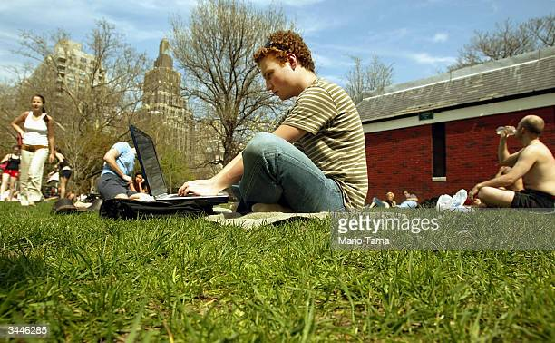 New York University student David Chines works on his laptop computer in Washington Square Park April 19 2004 in New York City Temperatures reached...