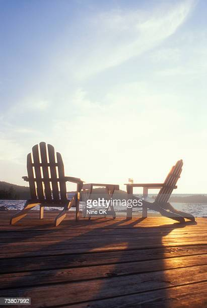 USA, New York, Upper Saranac Lake, Adirondack chairs on jetty at sunset