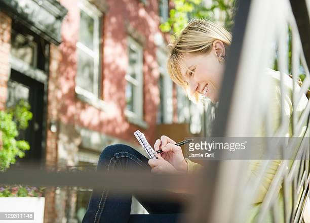 USA, New York, Williamsburg, Brooklyn, Smiling woman writing diary
