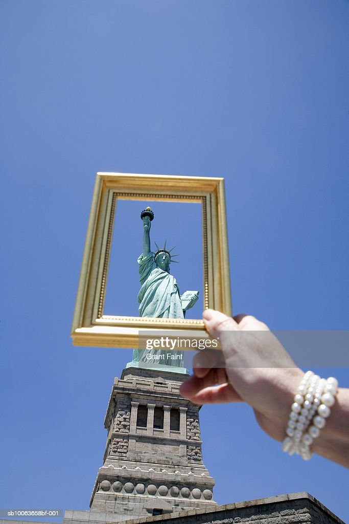 Usa New York Woman Holding Picture Frame In Front Of Statue Of