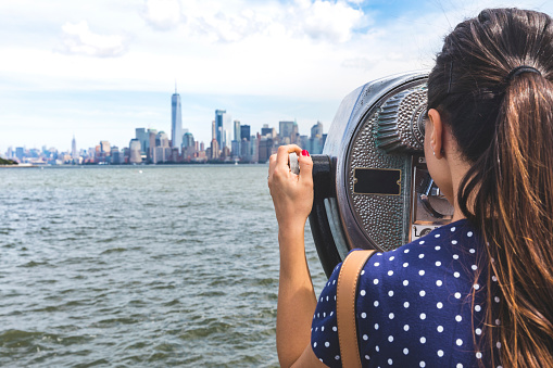 USA, New York, woman looking at Manhattan skyline with coin-operated binoculars - gettyimageskorea