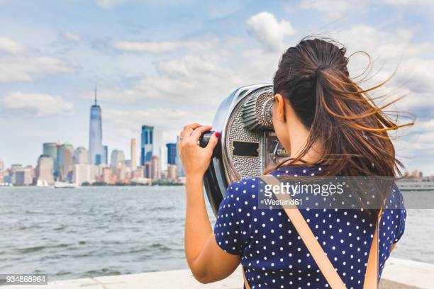 USA, New York, woman looking at Manhattan skyline with coin-operated binoculars