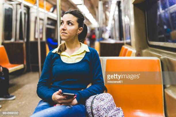 usa, new york, woman with cell phone in subway - subway train stock pictures, royalty-free photos & images