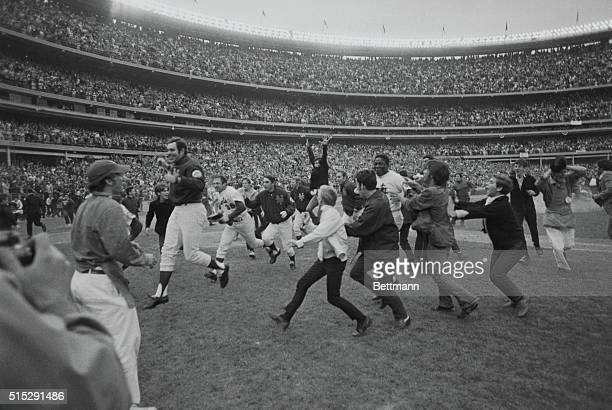 World Series champion New York Mets dash for safety of the dugout trying to outdistance jubilant fans who swarmed past guards onto the field 10/16