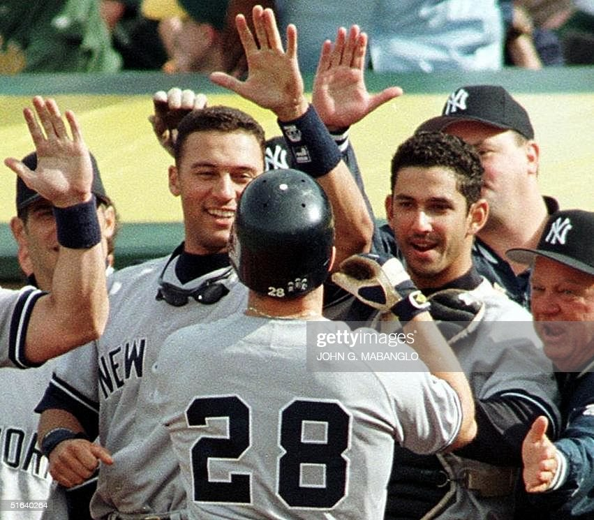 New York Yankee Chad Curtis (C) is greeted by bench coach Don Zimmer (R) and teammates after hitting a two-run homerun against the Oakland Athletics 05 April in Oakland, California. The Yankees defeated the A's 9-7 in their first win of the season. AFP PHOTOS John G. MABANGLO