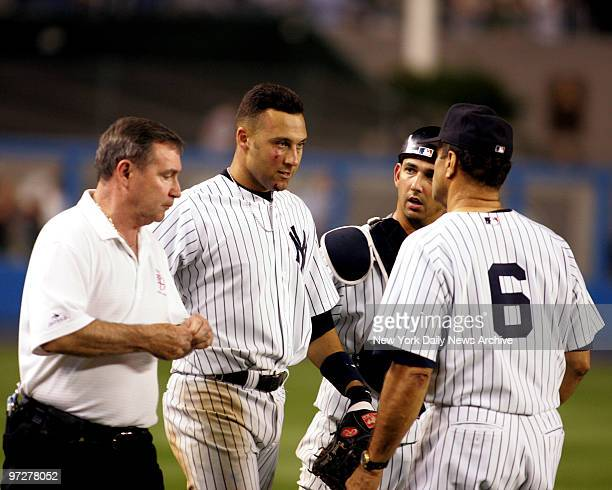 New York Yankee Derek Jeter with bruised and bloodied face head back to dugout after making run-saving catch on popup by Boston's Trot Nixon in 12th...