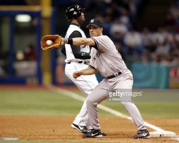 New York Yankee infielder Tino Martinez takes the pickoff throw from the pitcher as Tampa Bay Devil Rays outfielder Carl Crawford hurries back to...