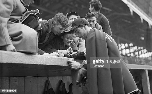 New York Yankee outfielder Joe Dimaggio, wrapped in a blanket in the cold weather, signs autographs for eager young fans above the dugout before a...