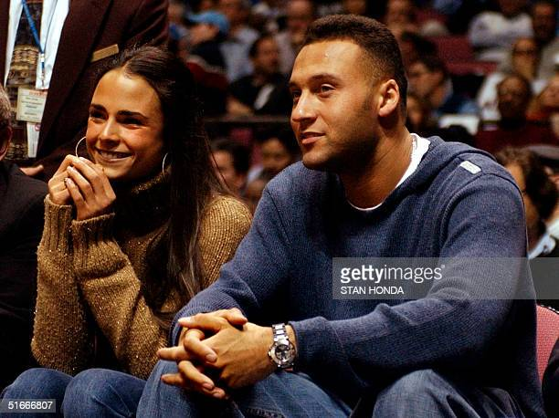 New York Yankee shortstop Derek Jeter and actress Jordana Brewster sit courtside 19 December 2002 at Continental Arena in East Rutherford New Jersey...