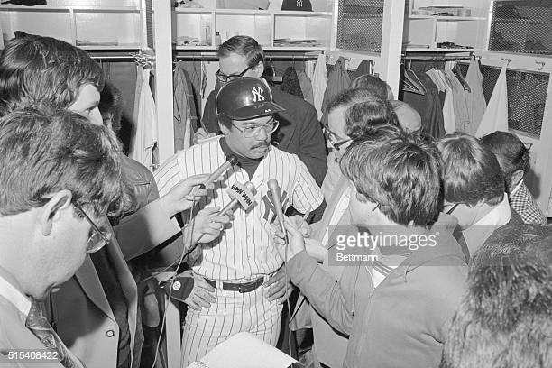 Yankee slugger Reggie Jackson is in full uniform while fielding surrounding newsmen's questions in dressing room after his team's victory over...