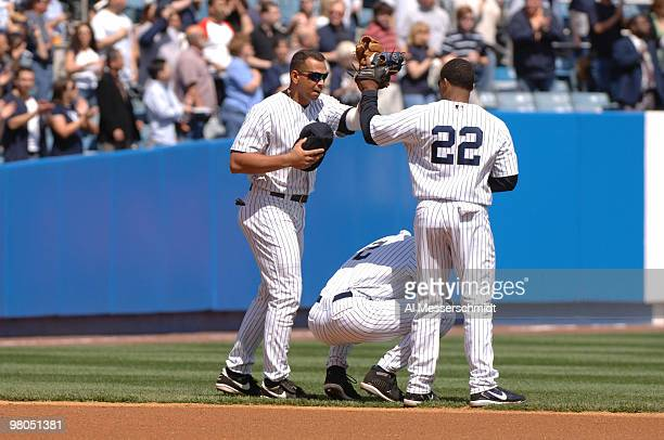 New York Yankees Alex Rodriguez and Robinson Cano hiugh five as Derek Jeter says a prayer before play against the Kansas City Royals April 13 2006 in...