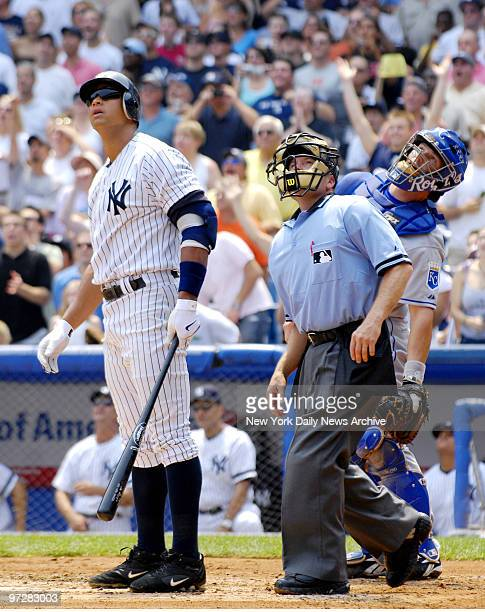 New York Yankees' Alex Rodriguez home plate umpire Jerry Meals and Kansas City Royals catcher Jason LaRue follow the path of a ball hit by Rodriguez...