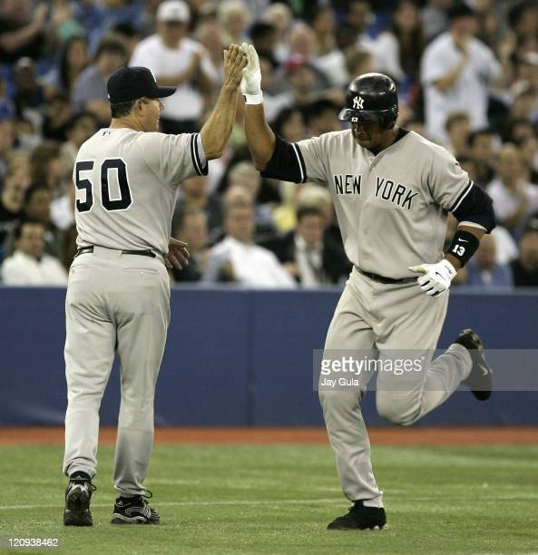 New York Yankees Alex Rodriguez is congratulated by 3rd base coach Larry Bowa after hitting his 34th HR of the season a 2 run shot in the 6th inning...